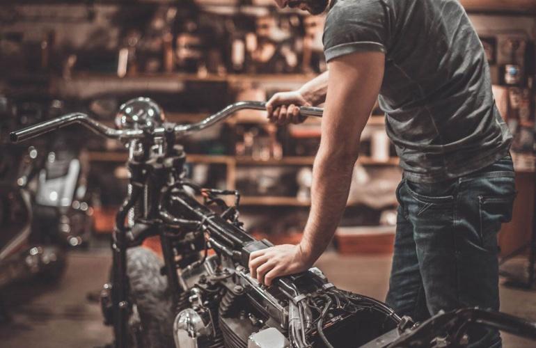 Мужчина держит мотоцикл